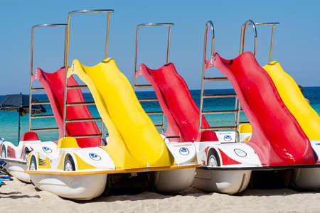 Colorful pedal boats with slides for rent on sandy beach with blue sea water Imagens