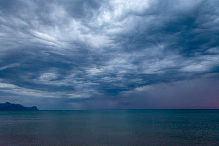 Scenic gray-blue clouds during sunrise over coastline with sandy beach in Alcamo Marina, small town in Sicily, Italy, summer vacation destination