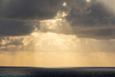 Dramatic sunset over sea water with gray clouds and sun lights, nature seascape