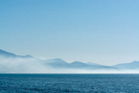 Seascape with low fog clouds over sea water in early morning with sun lights, nature background Reklamní fotografie