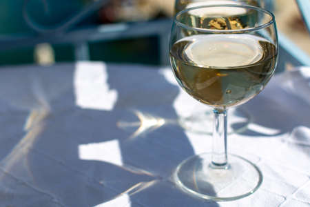 White wine served outside on balcony on glass table with sea view close up