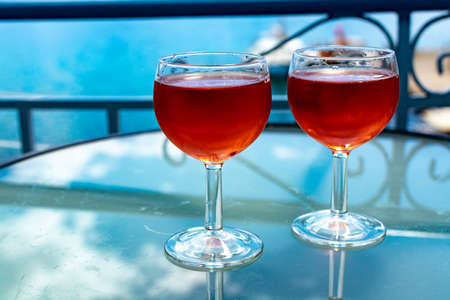 Rose wine served outside on balcony on glass table with sea view close up 写真素材