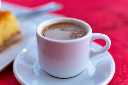 Traditional greek coffee served in white coffee set in cafe close up Imagens