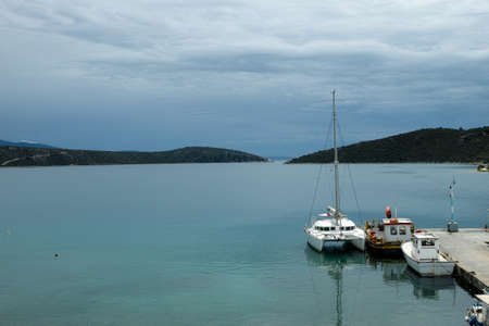 Seascape with cozy sea bay and big white catamaran yacht boat, vacation destination