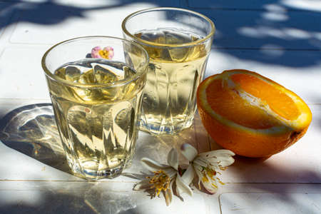 White wine served outside in garden on white table with fresh orange in sun lights close up Stock Photo