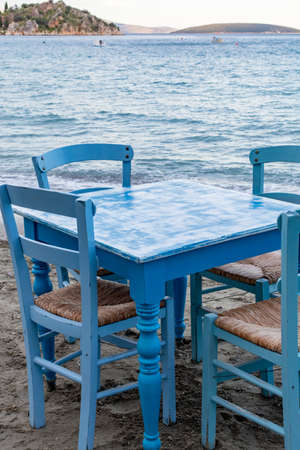 Traditional greek tavern with wooden tables on sandy beach near water waiting for tourists in Tolo, Peloponnese, Greece, vacation season is starting Reklamní fotografie