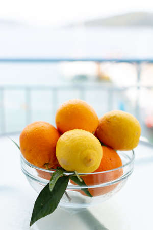 New harvest of tasty organic oranges and lemons, citrus fruits in glass bowl outside with sea view Imagens
