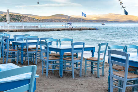 Traditional greek tavern with wooden tables on sandy beach near water waiting for tourists in Tolo, Peloponnese, Greece, vacation season is starting Stock Photo