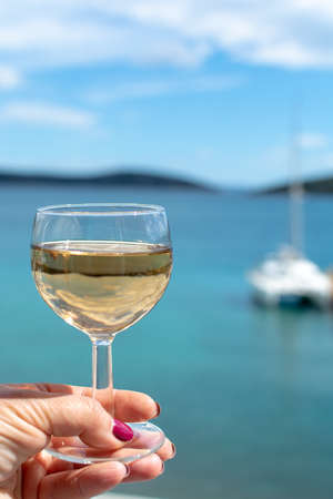 hand with glass of white wine served outside on balcony with sea view close up