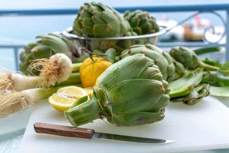 Preparation of heads of fresh raw green artichokes plants from artichoke plantation, new harvest in Argolida, Greece, ready to cook with fresh lemon Banco de Imagens