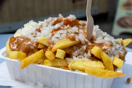 Traditional Dutch fast food dish, fried potatoes with sate sauce, onion and mayonaise, fat and not healthy street food close up