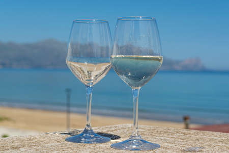 Two wine glasses with white wine served on outdoor terrace witn blue sea and mountains view on background in sunny summer day Banco de Imagens