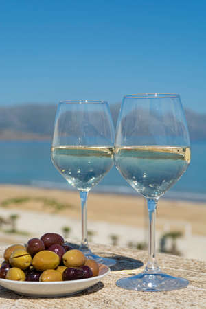 Two wine glasses with white wine served with olives on outdoor terrace witn blue sea and mountains view on background in sunny summer day Banco de Imagens