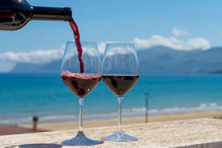 Waiter pouring red wine in wine glasses on outdoor terrace witn blue sea and mountains view on background in sunny day
