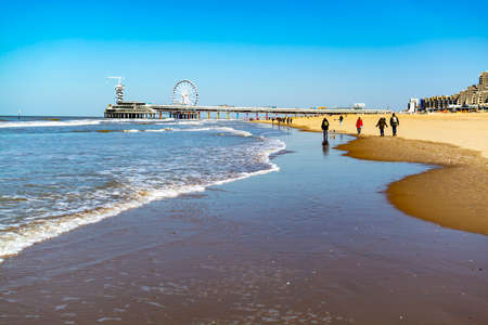 People walking in sunny day on North sea beach in Netherlands near Schegeningen, tourist and vacation destination in Europe