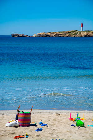Crystal clear blue water of  Mediterranean sea on St.Croix Martigues white sandy beach and colorful kids beach toys, Provence, France, vacation destination