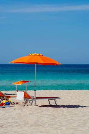 Service on beach, colorful sun bed and parasol for rent on beautiful white sandy beach with crystal clear blue sea water in sunny day