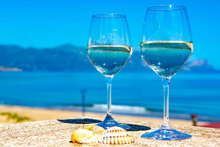 Two wine glasses with white wine served on outdoor terrace witn blue sea and mountains view on background in sunny summer day 스톡 콘텐츠