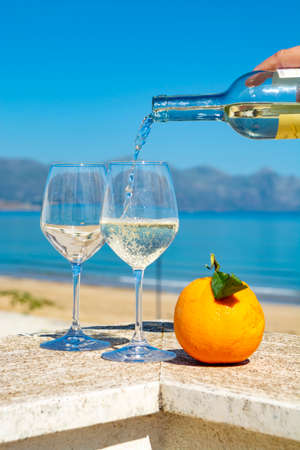 Waiter pouring white wine in wine glasses on outdoor terrace witn blue sea and mountains view on background in sunny day
