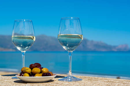 Two wine glasses with white wine served with olives on outdoor terrace witn blue sea and mountains view on background in sunny summer day Reklamní fotografie