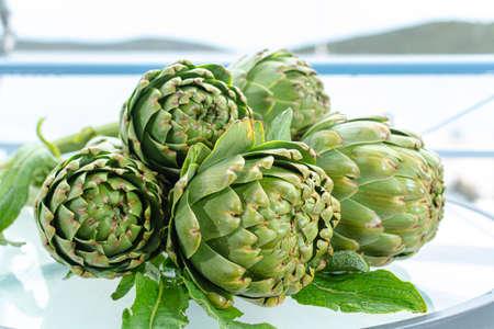 Bündel frische rohe Artischockenköpfe von der Artischockenplantage, neue Ernte in Argolis, Griechenland, bereit zum Kochen Standard-Bild