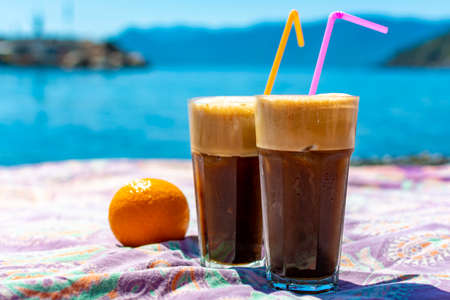 Traditional greek cold coffee Frappe with foam made from water, instant coffee and ice cubes in glass close up 写真素材