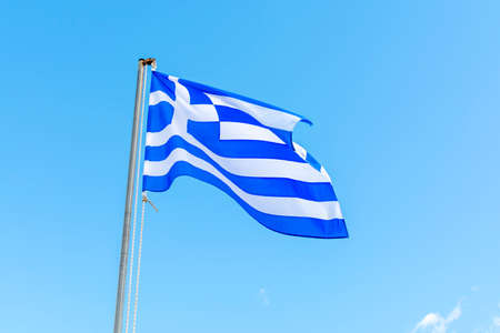 National symbol of Greece, blue-white greek flag on flagpole, sea water and blue sky, copy space