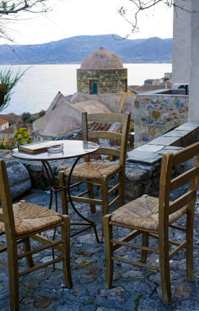 Greek cafe or tavern with small tables on outside terrace with nice view