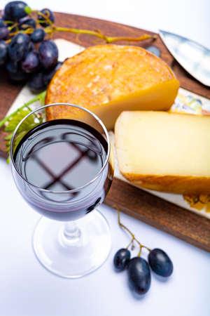 Hard Italian pecorino sheep cheese and glass with Italian red wine close up on white background