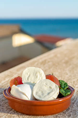 Cheese collection, Italian mozzarella soft cheese in balls served with tomatoes and fresh basil outdoor with blue sea view