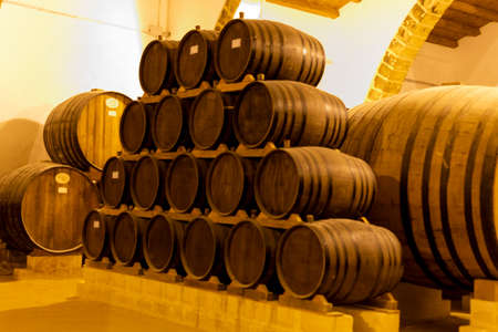 Vintage wine cellar with old oak barrels, production of fortified dry or sweet tasty marsala wine in Marsala, Sicily, Italy