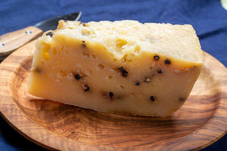 Cheese collection, Italian aged pecorino cheese with black peppers made in region Nebrodi, Sicily, Italy, close up