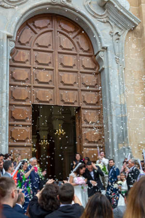 May 25, 2019, Marsala, Italy, Italian catholic wedding in church with many happy guests and salute from papers and rice