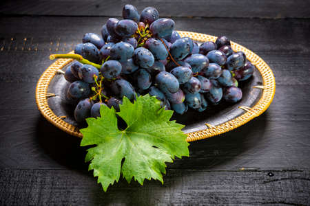Bunch of ripe blue-black table grapes with leaf served on black plate on black wooden background