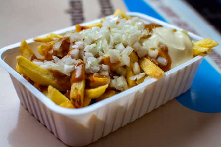 Eating of Belgian fried potatos chips with onion, sate and mayonnaise, street fast food, unhealthy food Фото со стока