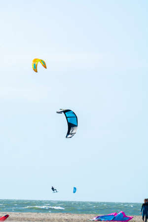 Water sport event, colorful kite surfers race in North Sea near Renesse, Zeeland, Netherlands