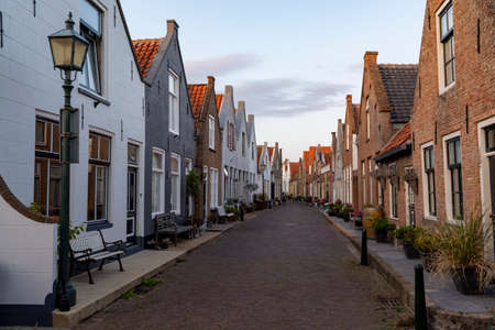 Street view with old houses in small Dutch town Goedereede on sunset, Zeeland, Netherlands Фото со стока