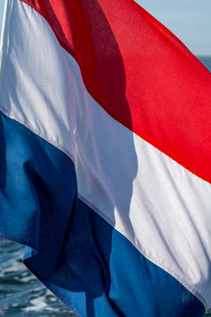 Dutch red white blue flag on sea water background close up