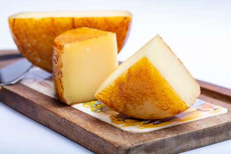 Twardy włoski ser owczy pecorino na drewnianej desce z bliska na białym tle