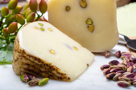 Cheese collection, Italian provolone or provola cheese made in Sicily with tasty green Bronte pistachio nuts served on white marble plate close up Фото со стока
