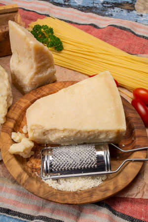 Cooking with hard italian cheese, grated parmesan or grana padano cheese close up Archivio Fotografico - 129038874
