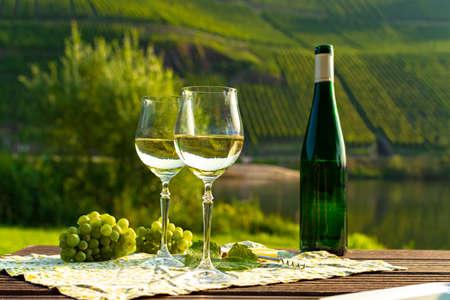 Berühmter deutscher Weißweinriesling, hergestellt in der Moselweinregion aus weißen Trauben, die an Hügelhängen im Moseltal in Deutschland wachsen, Flasche und Gläser werden draußen im Moseltal serviert served