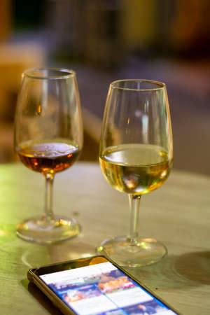 Always online with mobiel phone and sherry wine tasting, selection of different sweet jerez fortified wines made from pedro ximenez and muscat white grapes in Jerez de la Frontera, Andalusia, Spain