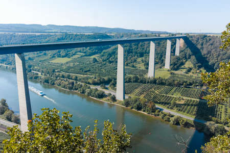 Panoramic view on high freeway viaduct bridge across Mosel river valley and terraced vineyards, road network and transportation is Germany