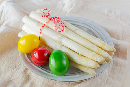 New harvest of white asparagus and colored Easter eggs, high quality raw asparagus in spring season, ingredients for Easter dinner close up Banque d'images