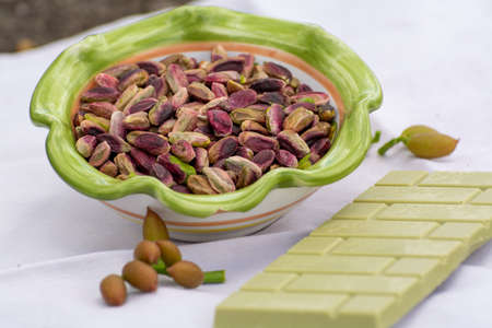 Sweet, delicate, fragrant nuts, Bronte pistachios with  brilliant green colour and handmade pistachio chocolate close up