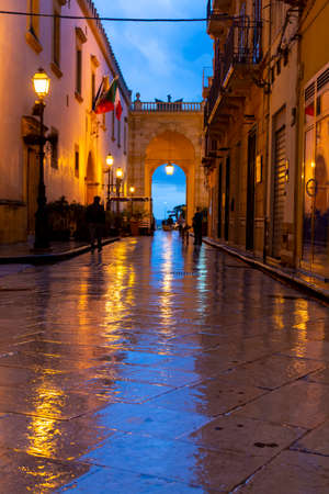 Old street in Marsala at night in rain with reflection of street lights, Sicily, Italy Stock fotó