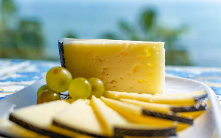 Spanish sheep cheese served with white grapes on andalusian style table outside with sea view Reklamní fotografie - 130755814