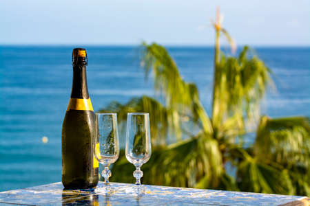 Romantic event, bottle with cold sparkling wine, cava or champagne served with two glasses on table with sea view and tropical palm tree Zdjęcie Seryjne - 130755816
