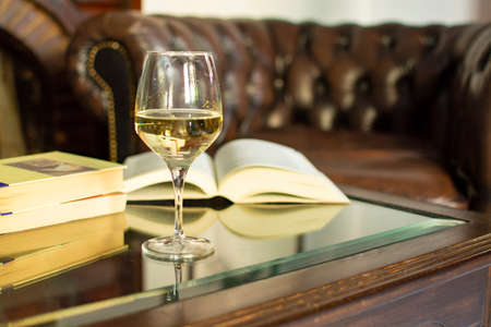 English retro style room with leather chair, open book on table and glas of white wine